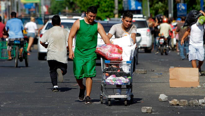 People push carts with goods after looting a supermarket during protests against the government's reforms in the Institute of Social Security in Managua, Nicaragua, on April 22, 2018.