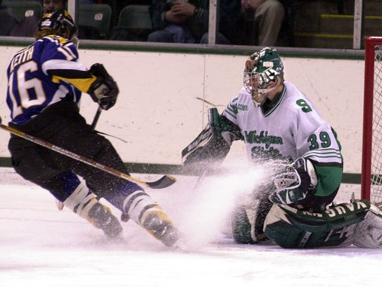 MSU goalie Ryan Miller, right, knocks away a shot from