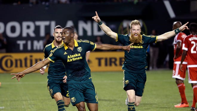 Portland Timbers forward Fanendo Adi, middle, celebrates his goal with teammates Nat Borchers, right, and Liam Ridgewell  during the second half of an MLS soccer match against the New England Revolution in Portland, Ore., Saturday, June 6, 2015.  Adi scored two goals as they beat the Revolution 2-0.