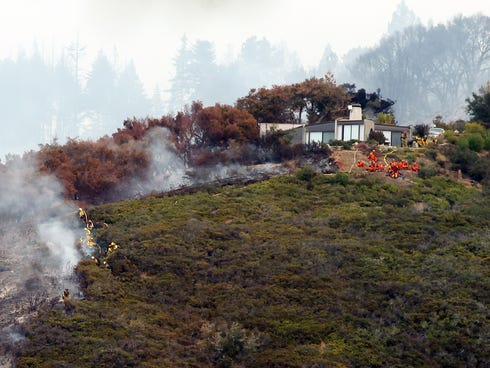 Fire crews work to contain the fire atop Pfeiffer Ridge, Monday, Dec. 16, 2013, in Big Sur, Calif. The wildfire burning Monday in the Big Sur area of California destroyed at least 15 homes and forced about 100 people to evacuate as it chewed through