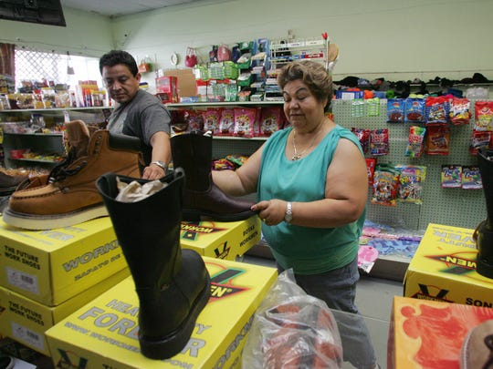 Eusevio Morga and his wife, Anna Medina, adjust the arrangement of imported work boots on display at their store, Ellie's Discount in Fillmore.