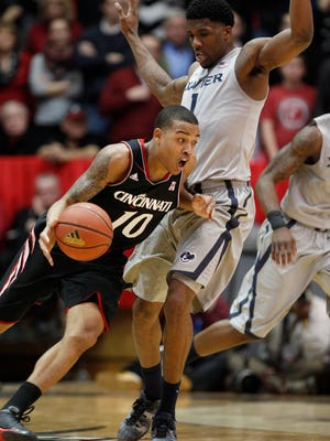 Cincinnati's guard Troy Caupain (10)drives the ball around Xavier's forward Jalen Reynolds (1) during the second half of their NCAA college basketball game, Wednesday, Feb. 18, 2015 in Cincinnati.  (AP Photo/Gary Landers)