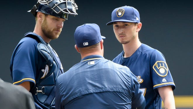 Brewers pitching coach Derek Johnson talks to pitcher Zach Davies (right) and catcher Jett Bandy on Sunday during a rough first inning for Davies.
