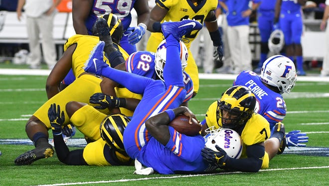Florida quarterback Malik Zaire is sacked by Michigan's  Mike McCray, under the pile, and Khaleke Hudson in the fourth quarter.
