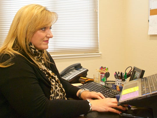 Lynn Figone, executive director of Ag Against Hunger, works at her desk at the group's offices at 1140 Abbott St., Suite C. in Salinas. The group shares space with the Monterey County Farm Bureau.