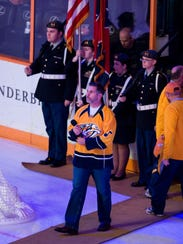 Dennis K. Morgan walks onto the ice to sing the national
