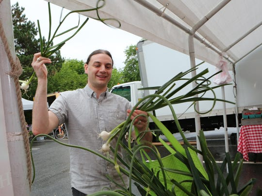 Mike Zollner from Port Chester checks out the garlic at the Mead Orchards booth at the Pleasantville Farmer's Market, June 20, 2015. In the summertime, he buys about 85% of his food items at various farmer's markets in the region.