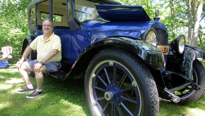 Ed Klug of Appleton sits with his 1921 Willys-Knight touring car Sunday at the Appleton Old Car Show and Swap Meet at Pierce Park. Klug's father owned the car before selling it two years ago. After his father's death, Klug bought the car back and surprised his family.