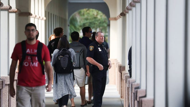 Florida Gulf Coast Police officers stand a few meters away from the entrance of Reed Hall on the FGCU campus on Tuesday. A new class called White Racism is being taught this semester. Police were standing by for any possible protests or disturbances. So far it has been business as usual.