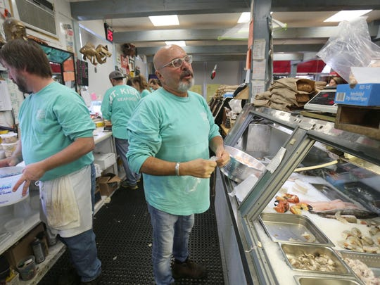 Owner Joe DiMauro chats with customers as they fill their Christmas Eve orders at Mount Kisco Seafood. The shop has been in operation for 43 years and brings in a DJ to entertain customers while they wait.