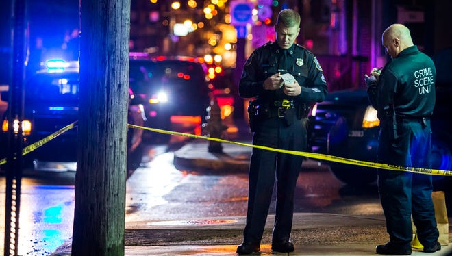 Wilmington police officers stand near the scene of a shooting near the corner of Maple Street and Maryland Avenue in Wilmington on Monday evening.