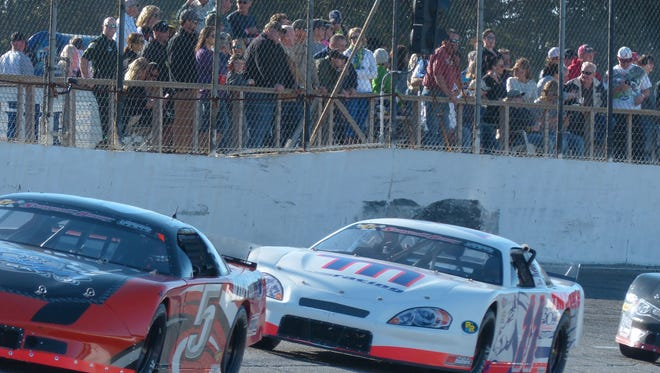 Race fans line the hand rails to watch the racing action in turn four of Five Flags Speedway during the 47th Snowball Derby Sunday afternoon.