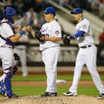 New York Mets catcher Kevin Plawecki, left, and Mets shortstop Wilmer Flores, right congratulate New York Mets starting pitcher Bartolo Colon (40) after he pitched into the eighth-inning of a baseball game against the Baltimore Orioles in New York, Tuesday, May 5, 2015.