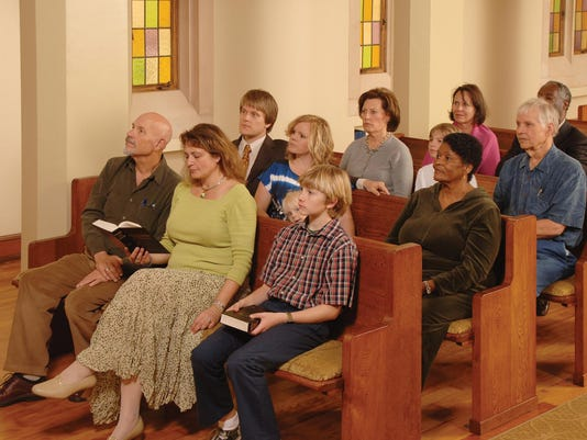 A church congregation sitting in pews listening to a sermon