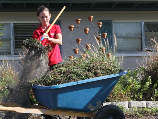 Samantha Cassaday of Mr. Handyman, removes the old grass from the yard of veteran Doug Hale in preparation for new sod during a National Day of Service on Wednesday.