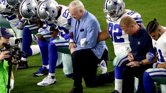 The Dallas Cowboys, led by owner Jerry Jones, center, take a knee before the national anthem at a game against the Arizona Cardinals last Monday.