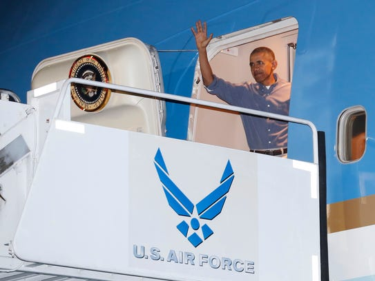 President Obama waves as he arrives on Air Force One
