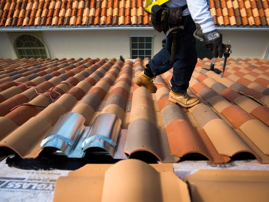 Marcos Cruz, a roofer with Ken Kelly Roofing, walks along a freshly tiled part of the roof on Thursday, February 1, 2018 in the Village Walk community in North Naples. Roofing companies are doing roughly 10 times the normal number of jobs, following Hurricane Irma.