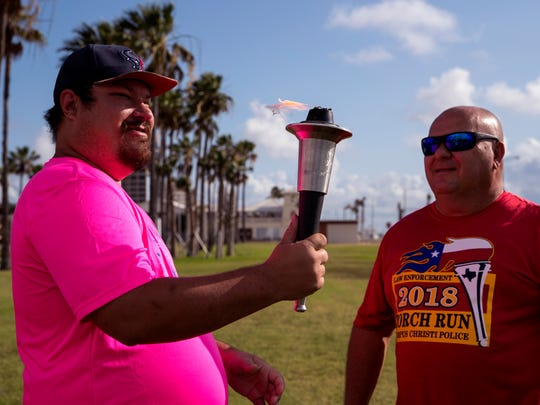 Robert Katocs (left) holds the Special Olympics torch just after Corpus Christi Police Lt. Henry Mangum lights it for the ceremonial run at Sherrill Park on Wednesday, May 23, 2018. The department will be sending a team to Arlington for the Special Olympics Summer Games. This is the 50th anniversary of Special Olympics.