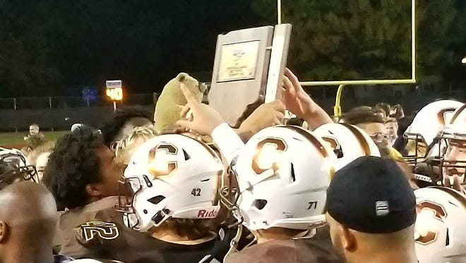 The Central High School football team celebrates with their IHSAA Class 4A Sectional 24 championship trophy.