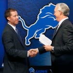 New Detroit Lions general manager Bob Quinn, left, is greeted by team president Rod Wood on Jan. 11, 2016, in Allen Park.