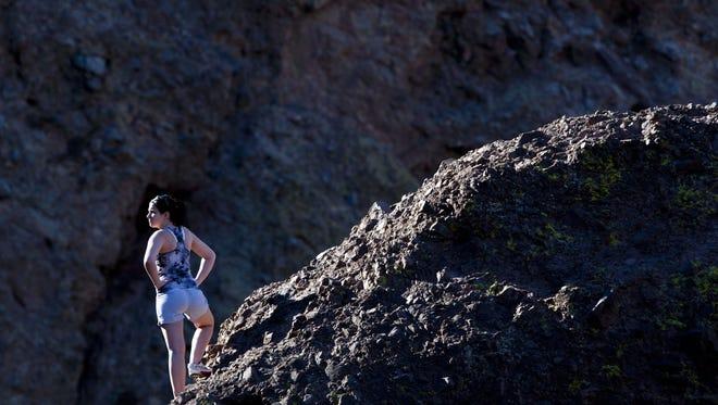 Erika Bateman of Pocatello, Idaho, climbs up a rocky ridge off of the Echo Canyon trail for Camelback Mountain in Phoenix on Wednesday, January 25, 2012.