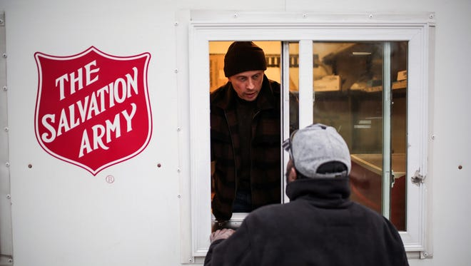 Free Press columnist John Carlisle works on the Salvation Army's Bed and Bread Club food truck.