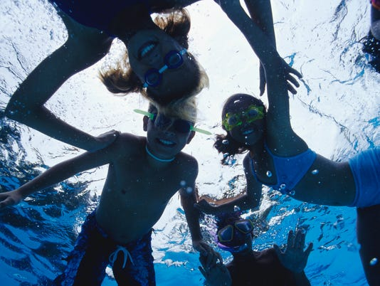 Group of children swimming in pool, underwater view, low angle view