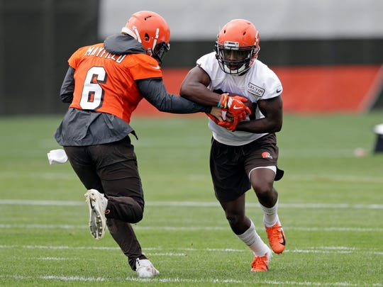 Cleveland Browns quarterback Baker Mayfield, left, hands the ball off to running back D'Ernest Johnson during an NFL football organized team activity session at the team's training facility on May 30 in Berea, Ohio. Johnson is one of four Immokalee NFL players conducting a camp on July 13.