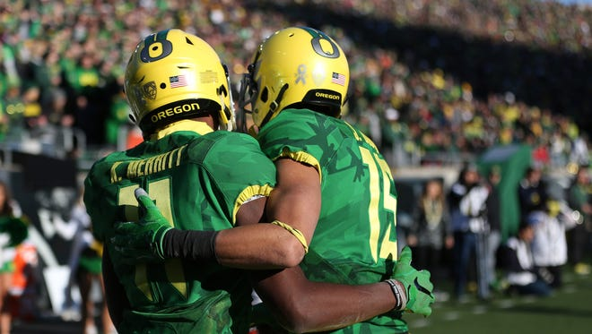 Oregon's Kirk Merritt and Jalen Brown embrace as the Ducks defeat the Beavers 52-42 during Civil War Friday, Nov. 27, 2015, at Autzen Stadium in Eugene, Ore.