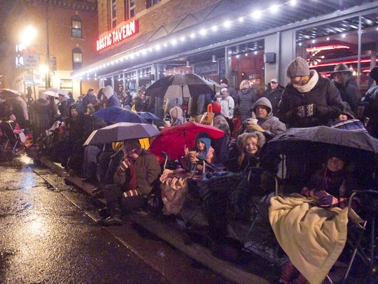 Despite a steady drizzle, a spirited crowd hunkered under umbrellas and blankets to witness the Fantasy of Lights Parade.