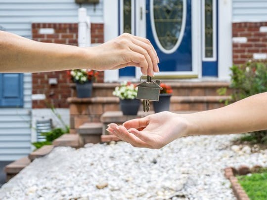 Woman handing house key over to another woman