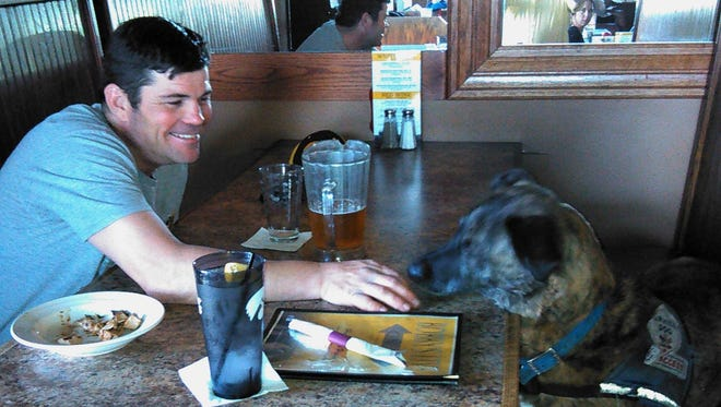 """Todd Bevans and his service dog, Arvo, relax in a bar booth in North Liberty. """"He's the best thing that has ever happened to me,"""" says Bevans, who copes with a brain injury from 17 years ago."""
