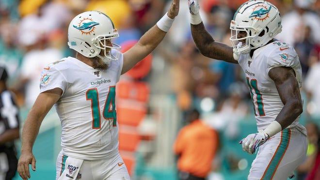 Dolphins quarterback Ryan Fitzpatrick high-fives receiver DeVante Parker after a last-minute touchdown against Washington.