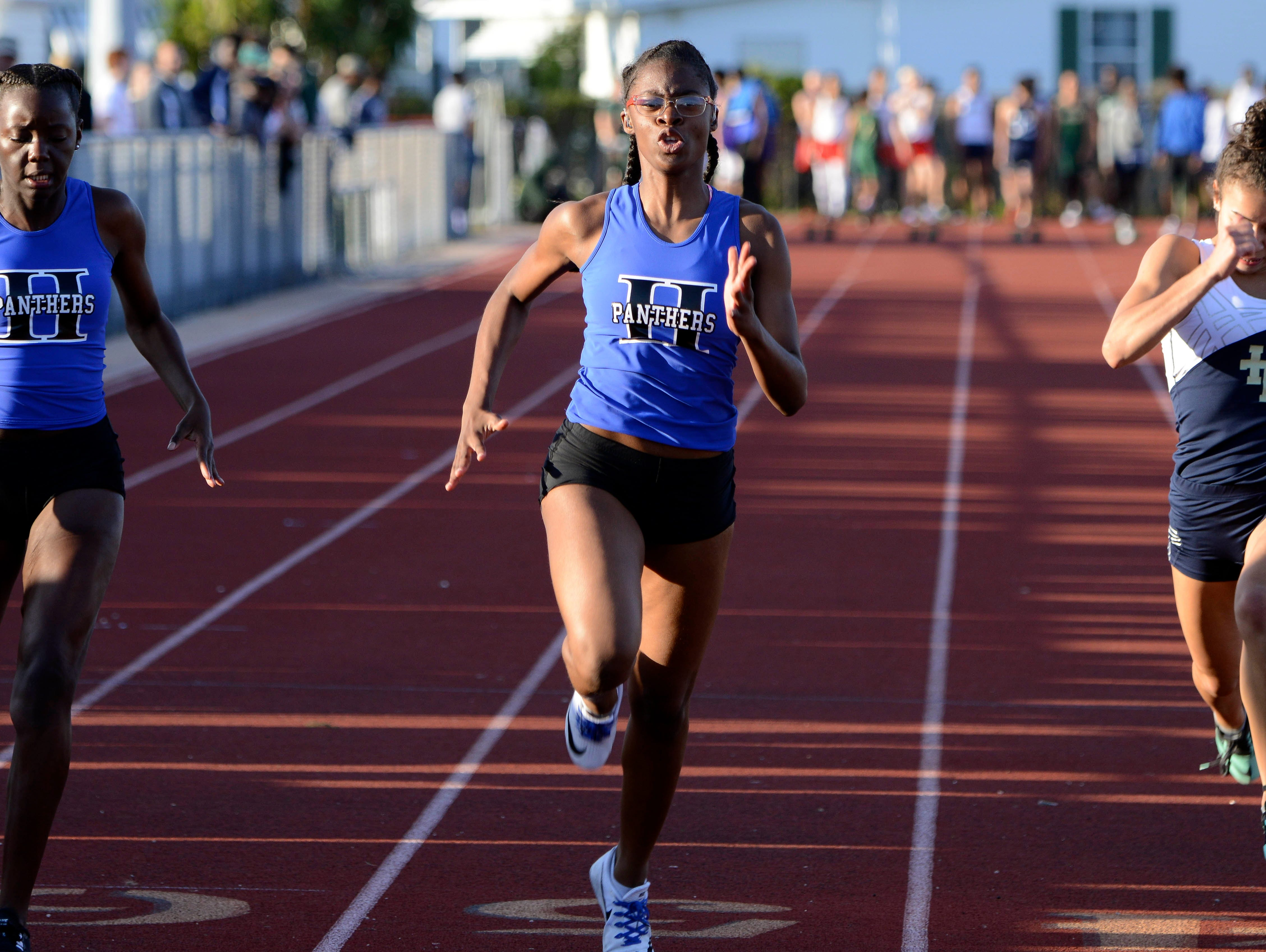 Jakia Alphonse of Heritage, Macoyah Barry of Heritage and Adriana Melendez of Holy Trinity run the 100 during Friday's track meet in Melbourne.