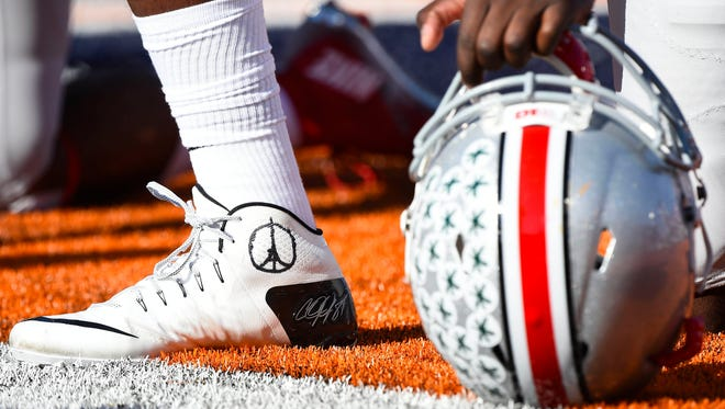 Ohio State Buckeyes quarterback Cardale Jones pays tribute to the victims of the attacks in Paris during a game against the Illinois Fighting Illini.