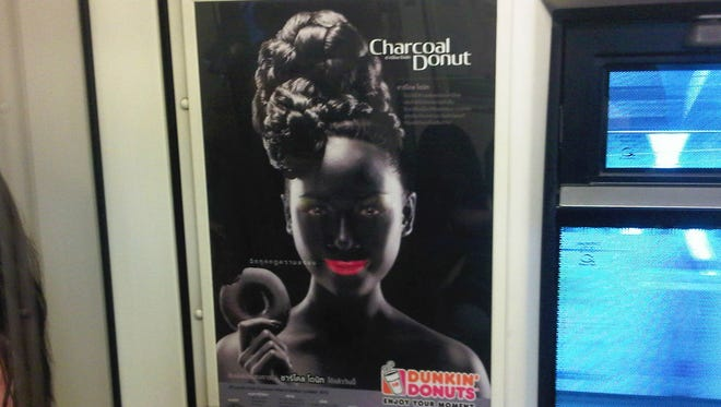 A poster of a smiling woman with bright pink lips in blackface makeup holding a doughnut is seen on a commuter train in Bangkok.