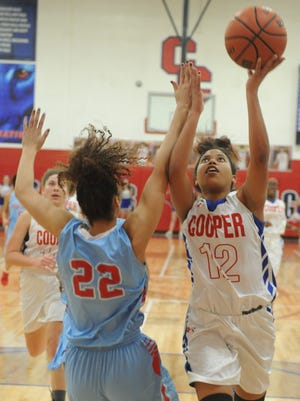 Cooper's T'Kiya Smith (12) drives to the basket as Lubbock Monterey's Braylyn Dollar (22) defends. Monterey beat the Lady Cougars 69-57 in the District 4-5A game Tuesday at Cougar Gym.