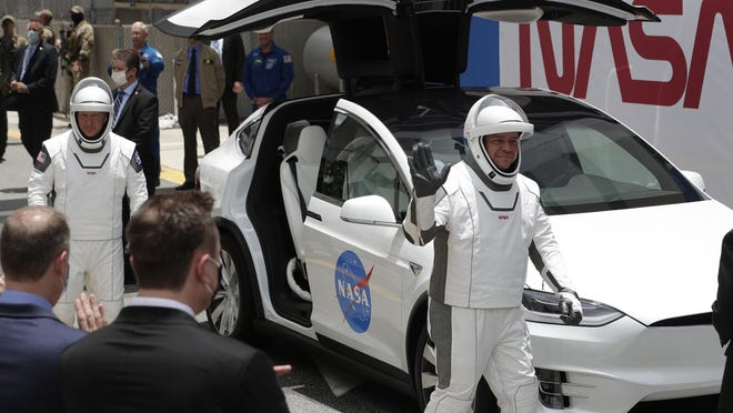 NASA astronauts Douglas Hurley, left, and Robert Behnken get ready to drive a Tesla SUV from the Neil A. Armstrong Operations and Checkout Building on their way to Pad 39-A, at the Kennedy Space Center.