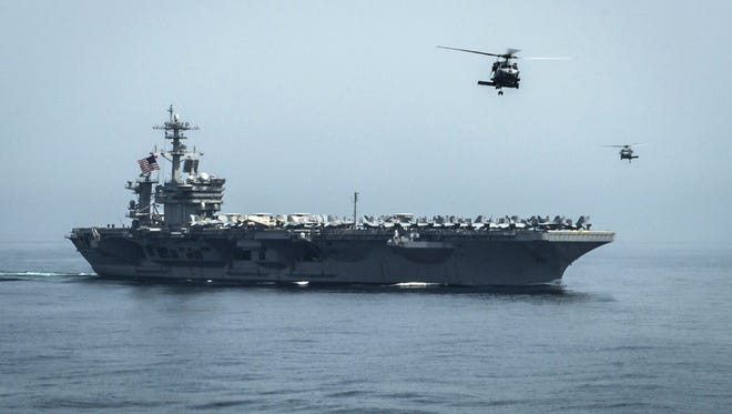 Helicopters fly from the aircraft carrier USS Theodore Roosevelt on April 13, 2015.