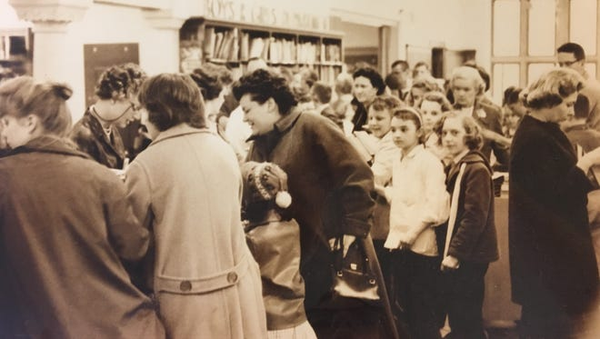 Library patrons circa 1960 check out items for the S.O.S. program.