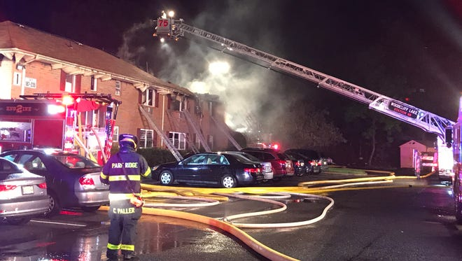 Firefighters work to put out flames at a condominium complex in Park Ridge on Friday night.