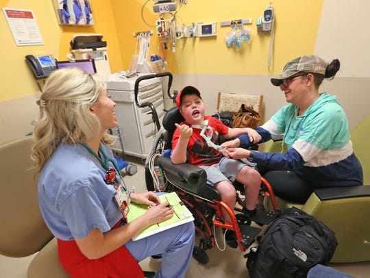Lauren Harper, left, laughs with patient Reese Garland,