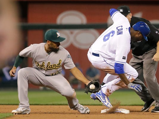Kansas City Royals' Lorenzo Cain (6) beats the tag at second by Oakland Athletics shortstop Marcus Semien after hitting a double during the fourth inning of a baseball game Wednesday, April 12, 2017, in Kansas City, Mo. (AP Photo/Charlie Riedel)