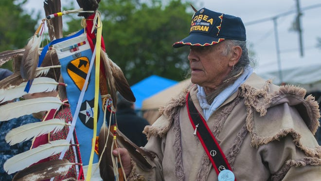 Korean War veteran Paul Yarnell, leads the Grand Entry with an Eagle Staff commemorating Native Americans who fought in the Korean War during the Riverbank Traditional Pow Wow on Sunday.