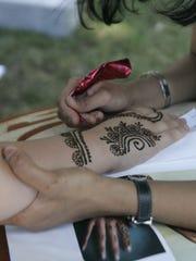 Rachel Jackson gets a temporary henna tattoo from Manisha