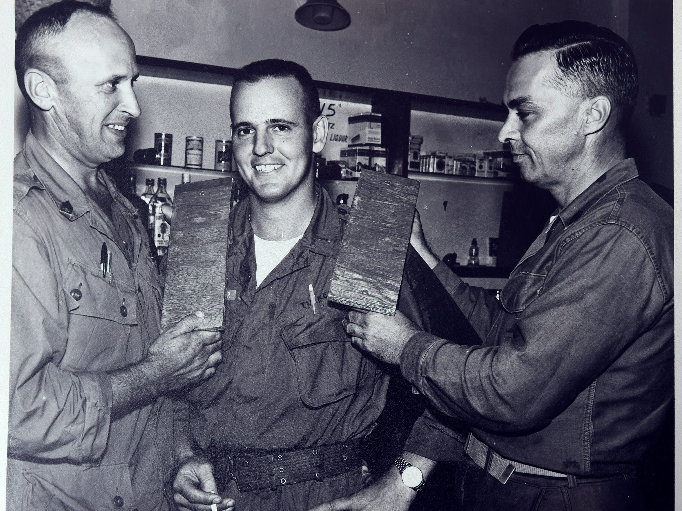 Vietnam veteran Fred Tucker, center, has his lieutenant bars put on his shoulders by his sergeants as a joke.