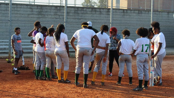 T.W. Josey's softball team has a word of prayer following a practice at Glenn Hills High School. Josey made history under third-year coach Dominique Davis as the first team in program history to qualify for the GHSA State Playoffs.