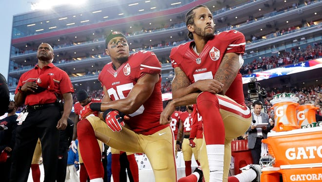 San Francisco 49ers safety Eric Reid (35) and quarterback Colin Kaepernick (7) kneel during the national anthem before an NFL football game against the Los Angeles Rams in Santa Clara, Calif.