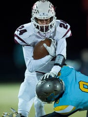 Henderson County's Max Hargis (24) gets tackled by